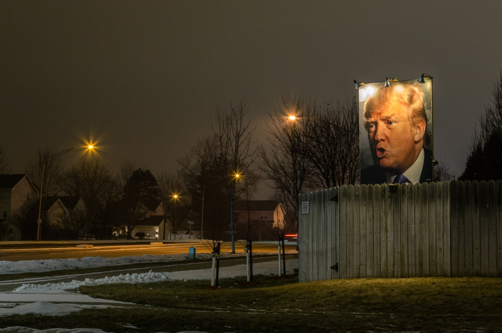 A photograph of 2016 presidential candidate Donald J. Trump lit up with flood lights in a suburban backyard near Jordan Creek Parkway and Cody Drive in West Des Moines, Iowa.
